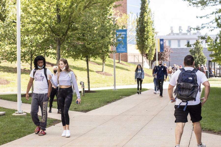 Students walk across campus wearing and not wearing masks.