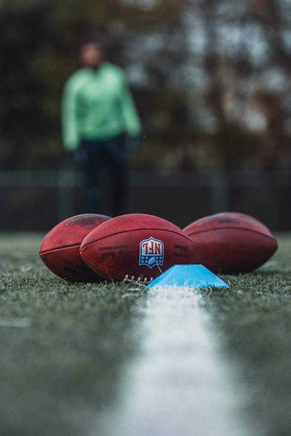 NFL footballs lay on a football field