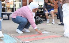 Adrielys Gomez draws the Puerto Rican flag on the sidewalk, Oct. 7, West Haven.