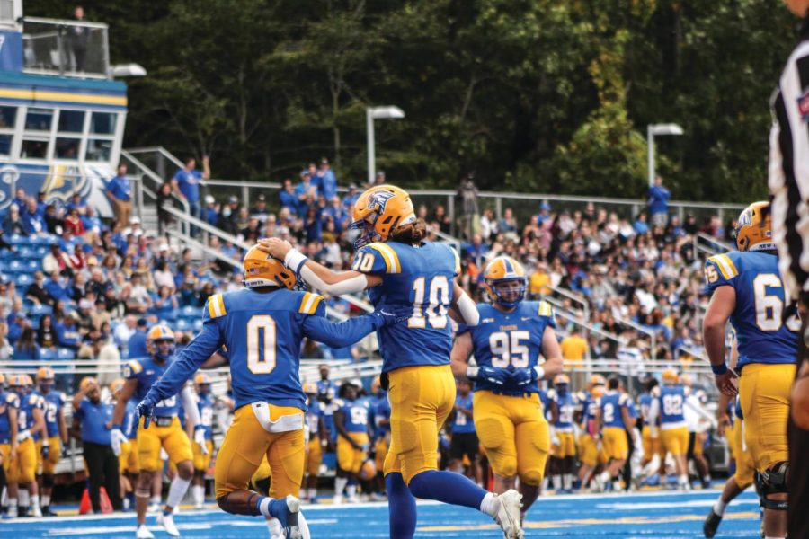 Dev Holmes, Connor Degenhardt and other players on the Chargers football team during the Homecoming football game versus Saint Anselm College, Oct. 9, West Haven.